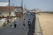 Friends walking along the seafront, Brooklands Estate in Jaywick Sands, Clacton-on-Sea. The estate's small wooden houses - many little bigger than beach huts - were originally built as holiday homes.... - Philip Wolmuth - 03-08-2011