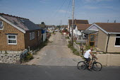Most roads on the Brooklands Estate in Jaywick Sands, close to Clacton-on-Sea are unadopted, without street lighting and in serious disrepair. The estate's small wooden houses - many little bigger tha... - Philip Wolmuth - 2010s,2011,age,ageing population,beach,BEACHES,chalet,chalets,COAST,coastal,coasts,deprivation,dilapidated,EBF,Economic,Economy,elderly,EQUALITY,excluded,exclusion,HARDSHIP,highway,holiday,HOLIDAYS,ho