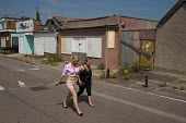 Teenagers walking along the dilapidated streets, with mobile phone. Boarded-up shops on the Brooklands Estate in Jaywick Sands, close to Clacton-on-Sea. Brooklands is the most deprived ward in the UK,... - Philip Wolmuth - 03-08-2011