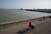 Farther pushing a pushchair, Clacton pier, Clacton-on-Sea, Essex. - Philip Wolmuth - 2010s,2011,coast,coastal,coastline,coastlines,coasts,holiday,holiday maker,holiday makers,holidaymaker,holidaymakers,holidays,leisure,LFL,LFL lifestyle & leisure,LIFE,OCEAN,PEOPLE,pier,pram,prams,push