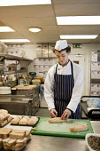 Apprentice cook at the Holiday Inn hotel, Bloomsbury, London. Baking bread loaves. - Philip Wolmuth - 21-02-2011