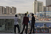 Young men look out over the London 2012 Olympic construction site from Westfield Stratford City, the largest urban shopping centre in Europe. - Philip Wolmuth - 15-09-2011