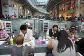 Women having their nails done. Westfield Stratford City, the largest urban shopping centre in Europe. - Philip Wolmuth - ,2010s,2011,asian,asians,BAME,BAMEs,bar,BARS,black,BME,bmes,bought,buy,buyer,buyers,buying,care,cities,city,commodities,commodity,complex,consumer,consumers,cultural,customer,customers,developer,devel