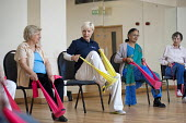 A chair-based keep fit exercise class at Swiss Cottage Community Centre. London - Philip Wolmuth - 2010s,2011,adult,adults,age,ageing population,band,bands,Camden,chair,chairs,cities,city,communities,Community,Cottage,COTTAGES,Council,elastic,elderly,employee,employees,Employment,exercise,exercises