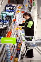 Worker stacking shelves, Asda supermarket, Clapham, London. - Philip Wolmuth - 28-11-2011
