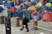 A businessman walks through the Occupy London camp outside St Paul's Cathedral. - Philip Wolmuth - 23-11-2011