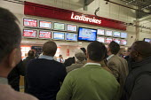 Men watch a televised horse race at a Ladbrokes bookmakers counter at Doncaster racecourse. - Philip Wolmuth - &,2010s,2011,bet,bets,betting,bookie,bookies,bookmakers,communicating,communication,counter,course,courses,domesticated ungulates,equestrian,equine,gambler,gamblers,gambling,HORSE,horse-racing,horses,