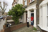 A Community Development Officer, Queens Park, does a door-to-door housing conditions survey in Bravington Road. - Philip Wolmuth - 2000s,2008,asian,asians,BAME,BAMEs,Bangladeshi,Bangladeshis,black,BME,bmes,cities,City,clipboard,clipboards,communities,Community,Council Housing,Council Housing,cultural,Development,diversity,employe