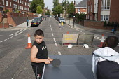 Children play table-tennis at a Tell It Parents Action Group street event to launch a drop-in advice service on the Mozart Estate, North Westminster, which has experienced problems with postcode gang... - Philip Wolmuth - 22-08-2011