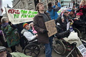 Wheelchair users chained together block the north side of Oxford Circus in a UK Uncut and Disabled People Against Cuts (DPAC) protest against the Welfare Reform Bill. - Philip Wolmuth - 28-01-2012