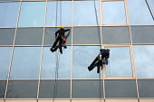 Two men clean the windows of an office building in Camden Town, London, using ropes and harnesses. - Philip Wolmuth - 14-02-2012