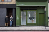 Two young workers take a break standing outside a hamburger bar with an ostrich in the window. Shoreditch, London, a run-down commercial district also known as Silicon Roundabout, which is undergoing... - Philip Wolmuth - 25-01-2012