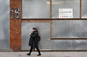 Woman walking past an empty office building in Shoreditch, London, a run down commercial district, also known as Silicon Roundabout, which is undergoing gentrification as it becomes a centre for web-b... - Philip Wolmuth - 07-02-2012