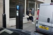 A young man uses a laptop in the street in Shoreditch, London, a run-down commercial district also known as Silicon Roundabout, which is undergoing gentrification as it becomes a centre for web-based... - Philip Wolmuth - 15-02-2012