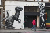 Mural of a rat following a woman on the wall of Rivington Studios, a 'Creative Office and Events Space' in Shoreditch, London, a run-down commercial district also known as Silicon Roundabout, which is... - Philip Wolmuth - 26-01-2012