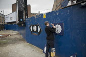 Daniel Burley, a student at Central St.Martins School of Art, assembles artwork on a hoarding in Shoreditch, London, a run-down commercial district also known as Silicon Roundabout, which is undergoin... - Philip Wolmuth - 06-03-2012