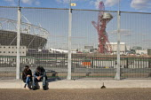 Two people rest by the security fence alongside the Olympic Stadium and Anish Kapoors ArcelorMittal Orbit sculpture, London 2012 Olympic Park, Stratford. - Philip Wolmuth - 2010s,2012,ACE,adult,adults,art,artist,ARTISTS,Arts,artwork,artworks,boyfriend,BOYFRIENDS,cities,city,communicating,communication,conversation,conversations,couple,COUPLES,Culture,depressed,depression