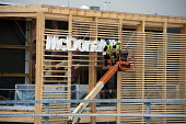 Workers erecting a McDonalds sign onto a new branch of the fast food restaurant chain in the Olympic Park, London. - Philip Wolmuth - 2010s,2012,builder,builders,building,building site,Building Worker,buildings,catering,cities,city,communicating,communication,Construction Industry,Construction Workers,EBF,Economic,Economy,EMPLOYEE,e