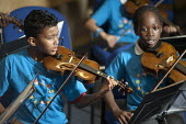 Schoolchildren from the Lambeth In Harmony project, which is based on the Venezuelan El Sistema music education programme devised by composer and social visionary Jos - Philip Wolmuth - 2010s,2012,BAME,BAMEs,black,BME,bmes,boy,BOYS,child,CHILDHOOD,children,cities,city,diversity,EDU,educate,educating,Education,educational,ethnic,ethnicity,female,females,girl,GIRLS,instruments,juvenile