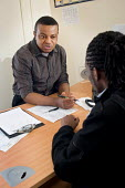 Employment advisor and client at Nova New Opportunities, in Ladbroke Grove, North Kensington. The area is home to a high proportion of recently arrived immigrants. - Philip Wolmuth - 2000s,2009,adult,Adult Education,adults,advice,ADVISE,ADVISER,advisers,advising,advisor,advisors,and,BAME,BAMEs,Basic Skills,bilingual,black,BME,bmes,cities,city,class,classroom,classrooms,communicati