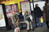 People waiting at a bus stop in Kilburn, London. - Philip Wolmuth - 22-11-2012