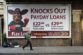 A pedestrian walks past an advertisement for loans at an interest rate of 1373% APR in Kilburn, London. - Philip Wolmuth - 2010s,2013,advertisement,advertisements,advertising,bank,bankers,banking,banks,borrowers,borrowing,business,cities,city,debt,debtors,debts,DOWNTURN,EARNINGS,EBF,Economic,Economy,EQUALITY,excluded,excl