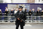 Police officer with a firearm. Funeral of ex-Prime Minister Margaret Thatcher, City of London. - Philip Wolmuth - 17-04-2013