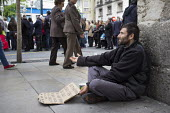 A homeless man begs on a street corner during a religious parade in Granada, Spain. - Philip Wolmuth - 18-05-2013