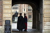 Two teachers in gowns at the entrance to Eton College. - Philip Wolmuth - 2010s,2013,adolescence,adolescent,adolescents,AFFLUENCE,AFFLUENT,board,boarder,boarders,Boarding School,Bourgeoisie,building,buildings,child,CHILDHOOD,children,EDU,educate,educating,Education,educatio