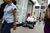 A City of Westminster street cleaner, employed by French multinational private contractor Veolia, sweeps the pavement outside shops in Oxford Street, London. - Philip Wolmuth - 05-08-2013