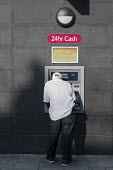 A man makes a withdrawal at an ATM cash machine, Cricklewood, London. - Philip Wolmuth - 29-08-2013