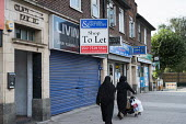 Two women wearing traditional dress pass empty shop premises to let in Cricklewood, London. - Philip Wolmuth - 2010s,2013,and,BAME,BAMEs,black,BME,bmes,bought,burka,burkas,burqa,burqas,business,businesses,buy,buyer,buyers,buying,cities,city,closed,closing,closure,closures,commodities,commodity,communicating,co