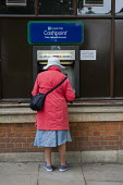 Elderly woman using a cash machine, Hamsptead, London. - Philip Wolmuth - 17-09-2013
