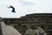 Parkour specialist practices a wall-to-wall leap, Buda Castle, Budapest. - Philip Wolmuth - &,2010s,2014,activities,Castle,cities,city,Extreme Sports,hobbies,hobby,hobbyist,Hungarian,Hungarians,Hungary,leisure,lfL,LIFE,lifestyle,Outdoor Activity,parkour,PEOPLE,PHYSICAL,recreation,RECREATIONA