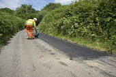Worker from contractor Lafarge Tarmac sealing a repair on a country road in Hereforshire. - Philip Wolmuth - 10-07-2014