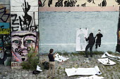 A street artist (name unknown) wearing a hoodie uses stencils to create a mural of children attacked by a drone in the style of Banksy on a wall bordering a well-used footpath along the Danube Canal,... - Philip Wolmuth - 03-07-2014