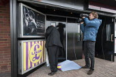 A member of staff removes UKIP posters outside the Movie Starr cinema, Canvey Island, South Essex, following the launch of the party's General Election campaign a the seafront venue. - Philip Wolmuth - (BP),2010s,2015,£B,Bristol Pound,cameraman,campaign,campaigning,CAMPAIGNS,cinema,COAST,communicating,communication,DEMOCRACY,Election,elections,employee,employees,Employment,Essex,eurosceptic,Eurosce