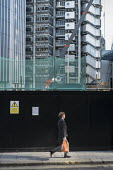A City of London worker walks past a construction site next to the Lloyds Building. - Philip Wolmuth - 17-02-2015