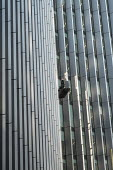 A maintenance worker inspecting windows from a cradle on a high-rise office block in the City of London. - Philip Wolmuth - 17-02-2015