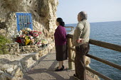 An elderly couple pay respects at a seaside shrine, La Cala del Moral, Malaga, Spain. - Philip Wolmuth - &,2010s,2015,adult,adults,age,ageing population,Andalusia,Andalusian,Belief,Catholic,catholicism,Catholics,Christian,christianity,christians,cities,city,cliff,cliffs,COAST,coastal,coasts,conviction,co