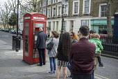 Queue for an ATM cash machine in a telephone box, a combined public payphone and cash machine. London. - Philip Wolmuth - 10-04-2015
