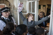 Police officers watch as Blue 9 private security guards prevent protesters from entering Hendon Town Hall through a window. Tenants, evicted tenants and housing campaigners in Barnet, north London, pr... - Philip Wolmuth - ,2010s,2015,activist,activists,adult,adults,Barnet,CAMPAIGN,campaigner,campaigners,CAMPAIGNING,CAMPAIGNS,CLJ,communities,community,Cornelius,Council,DEMONSTRATING,demonstration,DEMONSTRATIONS,develope
