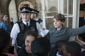 Police officers watch as Blue 9 private security guards prevent protesters from entering Hendon Town Hall through a window. Tenants, evicted tenants and housing campaigners in Barnet, north London, pr... - Philip Wolmuth - 13-05-2015