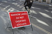 Narrow lanes do not overtake cyclists. Temporary warning sign on a road in central London. 14 cyclists were killed in road accidents in London in 2014. - Philip Wolmuth - 2010s,2015,accident,accidental,accidents,adult,adults,bicycle,bicycles,BICYCLING,Bicyclist,Bicyclists,BIKE,BIKES,cities,city,communicating,communication,COMMUTE,commuter,commuters,commuting,cycle,cycl