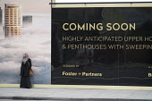 Woman waiting for a bus by a hoarding advertising new luxury housing by Foster and Partners, Shoreditch, London. - Philip Wolmuth - 2010s,2015,advertisement,advertisements,advertising,AFFLUENCE,AFFLUENT,apartment,apartments,BAME,BAMEs,Black,blocks,BME,bmes,Bourgeoisie,builder,builders,building,buildings,bus,bus service,BUSES,citie