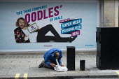 Homeless man rummaging through his possessions Oxford Street London Keith Lemon Carphone Warehouse advertisement - Philip Wolmuth - 2010s,2015,ad,adult,ADULTS,advertisement,advertisements,advertising,billboard,billboards,care,cities,City,communities,community,EQUALITY,excluded,exclusion,HARDSHIP,hoarding,homeless,homelessness,hous