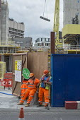Construction workers taking a break Rathbone Square office retail and residential redevelopment by Great Portland Estates behind Oxford Street London. - Philip Wolmuth - 19-08-2015