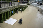 Roma trumpet player busking on the Thames South Bank London, watched by his wife and daughter. - Philip Wolmuth - 2010s,2015,Bank,BANKS,beach,BEACHES,busker,buskers,busking,cities,city,COAST,coastal,coasts,Diaspora,eastern,EQUALITY,eu,european,europeans,excluded,exclusion,foreign,foreigner,foreigners,gipsey,Gipse