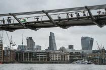 Tourists with umbrellas on the Thames Millennium Bridge London in heavy rain - Philip Wolmuth - 25-08-2015