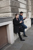 Two young men leaning on a wall check mobile phones in a London street - Philip Wolmuth - 29-09-2015